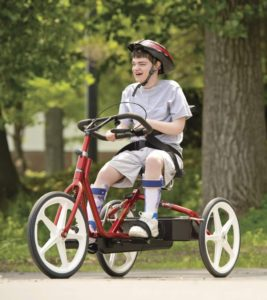 adolescent qui pédale sur un tricycle médical